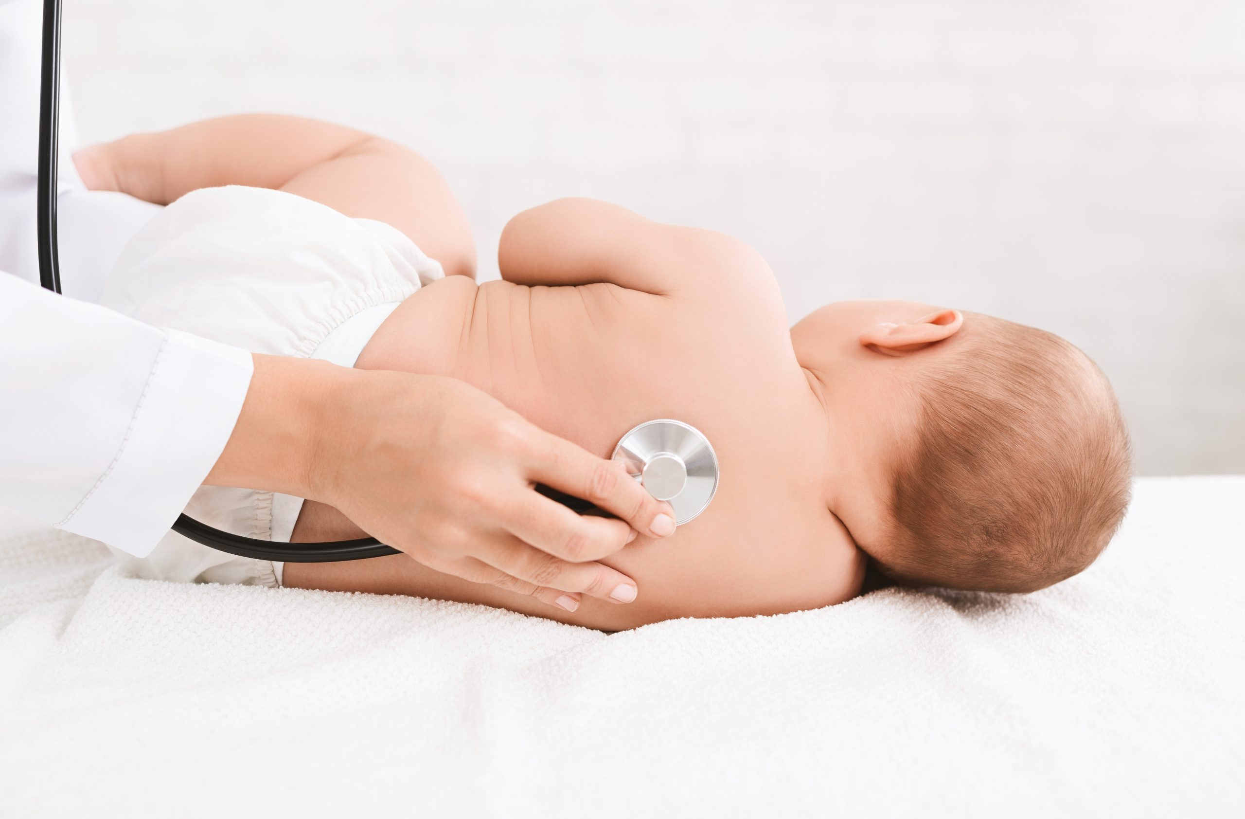 Children's doctor exams baby with stethoscope, listening his back in hospital