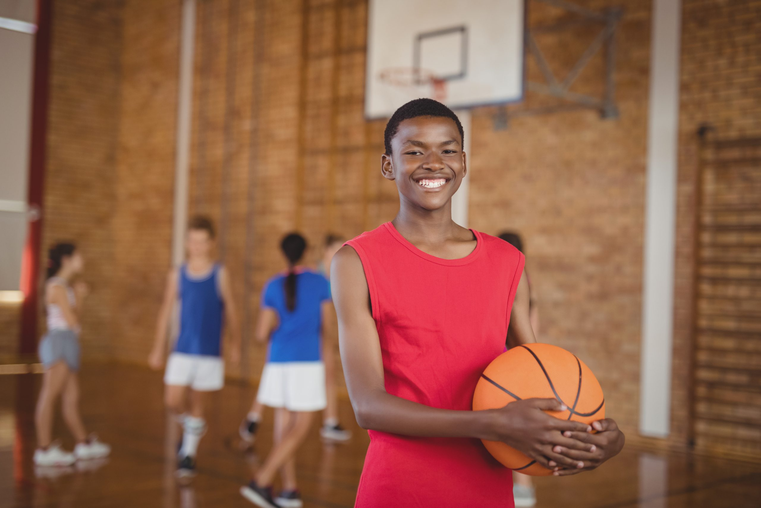Portrait of smiling school boy holding a basketball while team playing in background