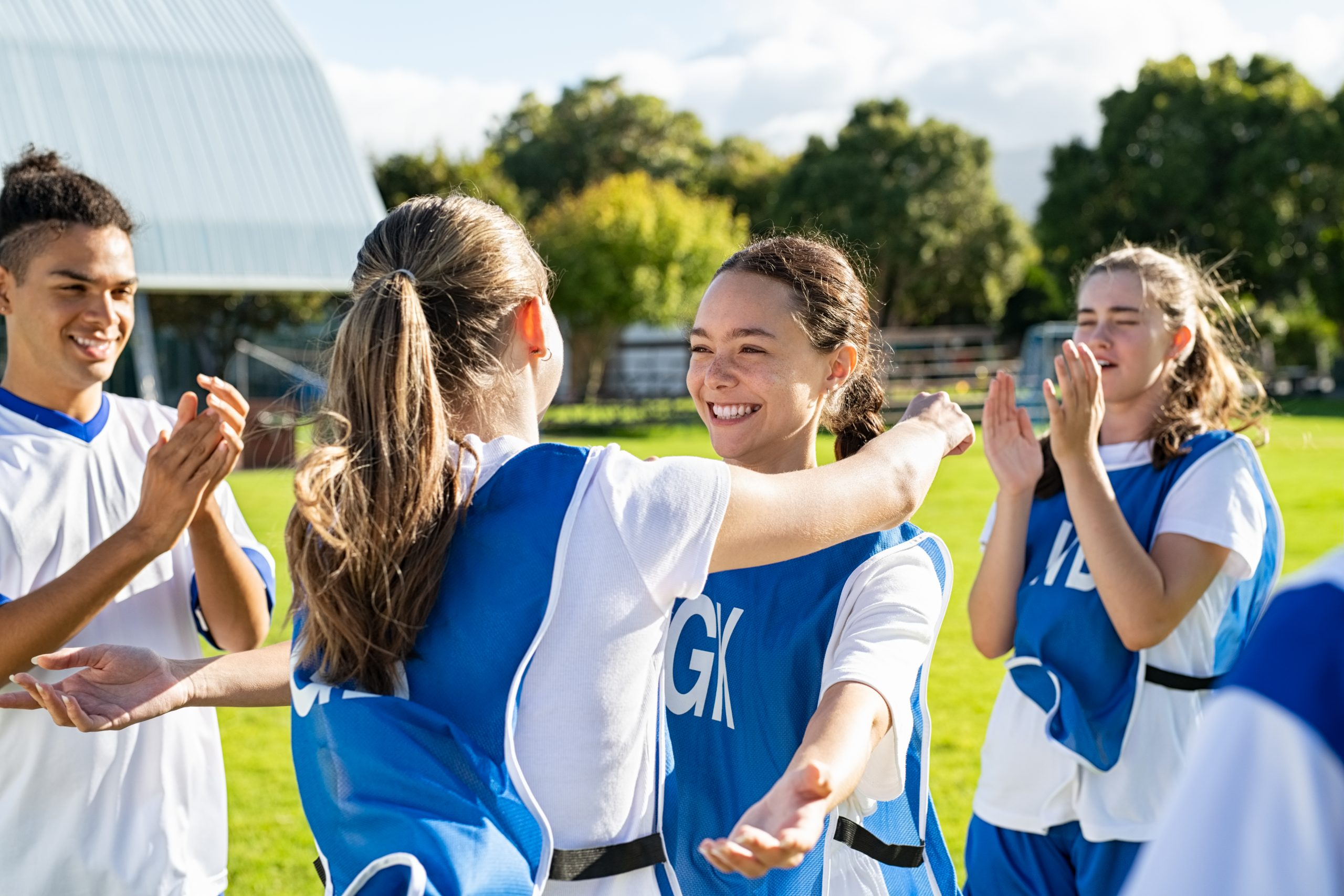 Young woman football players hugging with open arms after goal. College teammates hugging and celebrating victory. Two happy friends hugging on soccer field after sport match.